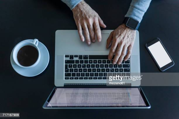 Top view of businessman at desk with laptop, smartphone and cup of coffee
