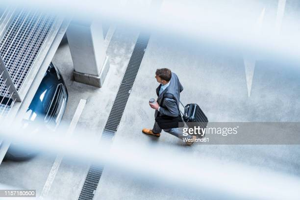 top view of businessman walking with baggage and takeaway coffee at a car park - geschäftsreise stock-fotos und bilder