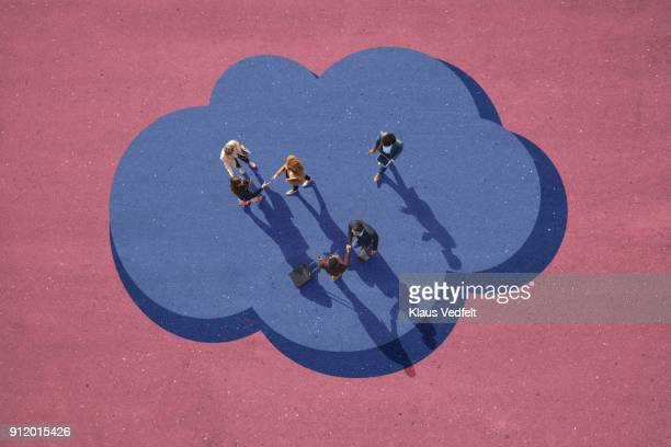 Top view of businesspeople making handshakes. Standing on painted cloud on asphalt