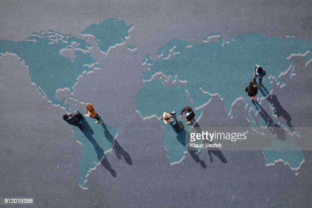 top view of businesspeople talking. standing on painted world map on asphalt - global village stock pictures, royalty-free photos & images