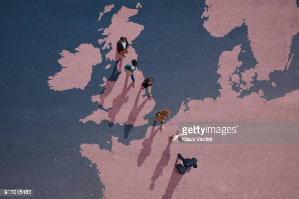 top view of businesspeople walking out of great britain on painted north european map - emigration and immigration stock pictures, royalty-free photos & images