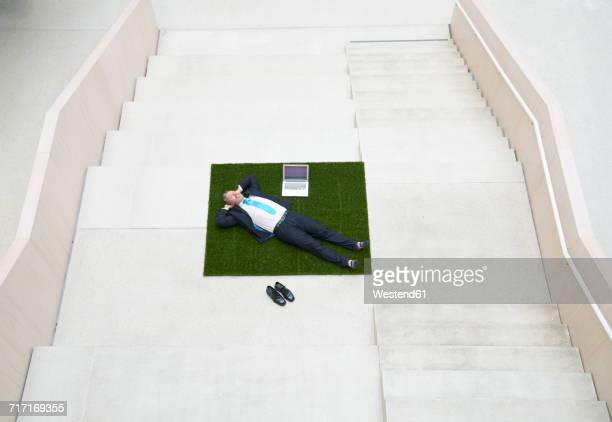 Top view of businesssman lying on stairs next to laptop