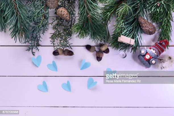 Top view of Christmas decorations: Elf, heart shape, acorn, pine cone, and fir tree with copy space on wooden background.