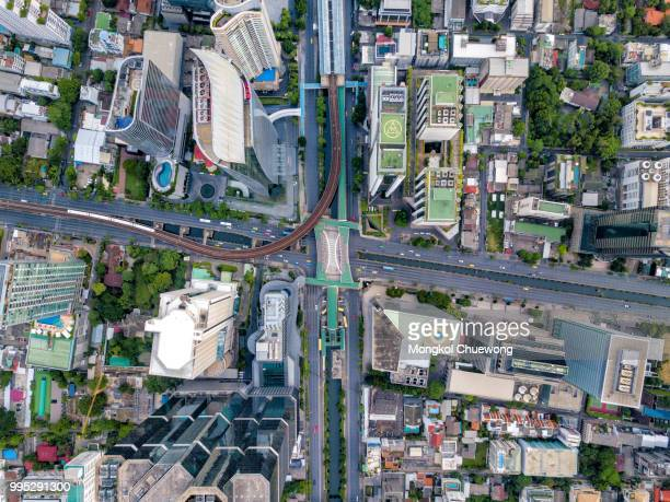 top view of city road junctions in heart of business center on sathorn and silom district at bangkok city thailand. aerial view of bts skytrain run into the smart city at bangkok downtown in thailand. - urban sprawl stock pictures, royalty-free photos & images