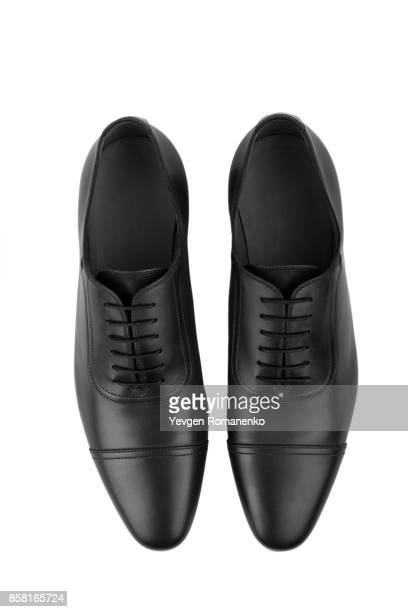 top view of classic black leather shoes on white - calzature di pelle foto e immagini stock