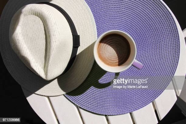 top view of coffee cup with straw hat on purple placemat - purple hat stock pictures, royalty-free photos & images
