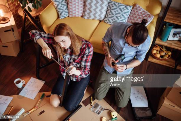 Top view of couple assembling new furniture