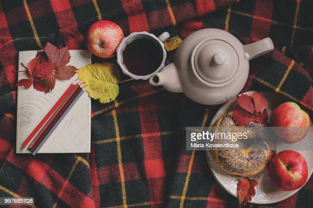 Top view of cozy autumn morning at home. Breakfast with pot of tea and bagel with apples on...