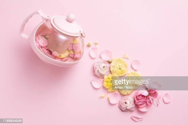 top view of creative layout of pink teapot and tea cup with flowers on pink background. - pale pink stock pictures, royalty-free photos & images