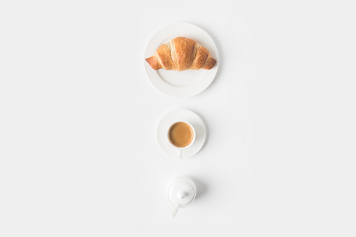 top view of cup of coffee and croissant for breakfast on white surface 916294626
