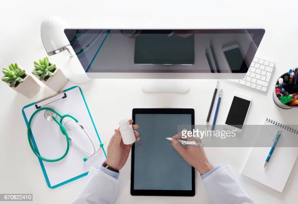 top view of doctor sitting at the desk and using digital tablet - izusek stock pictures, royalty-free photos & images