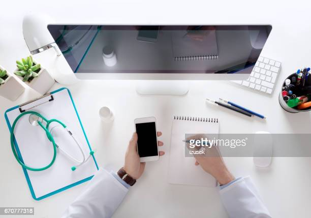Top view of doctor sitting at the desk and using smart phone