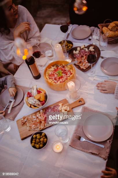 top view of family at traditional rustic mediterranean dinner table - antipasto stock photos and pictures