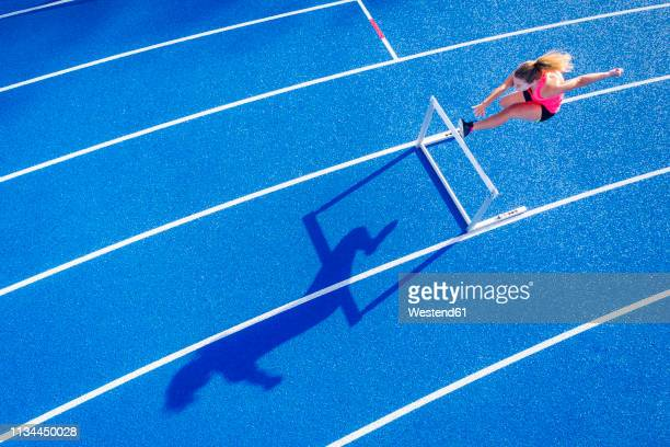 top view of female runner crossing hurdle on tartan track - hurdle stock pictures, royalty-free photos & images