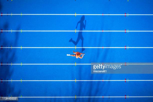top view of female runner on tartan track - laufwettbewerb der frauen stock-fotos und bilder