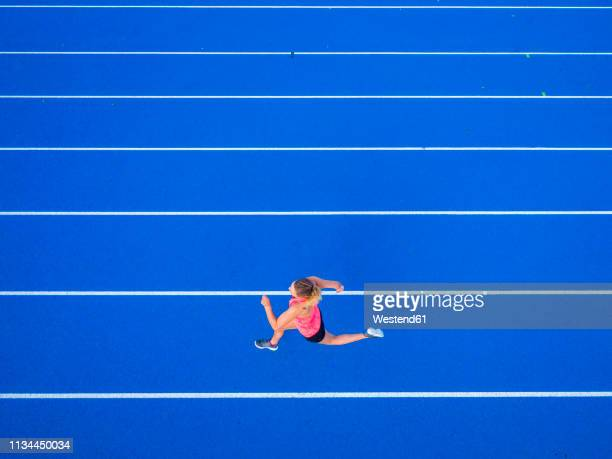 top view of female runner on tartan track - running track stock pictures, royalty-free photos & images