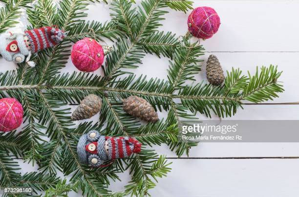 Top view of fir tree branch with Christmas ornaments on painted wood background with copy space.