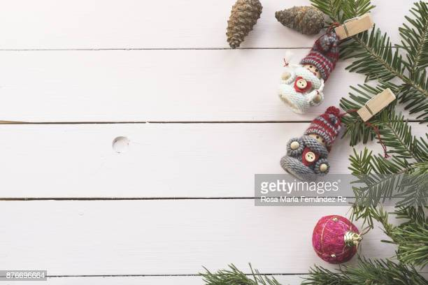 Top view of fir tree branch with Christmas ornaments on soft painted wood background with copy space.