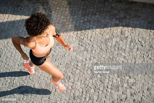 Top view of fitness woman running on pavement
