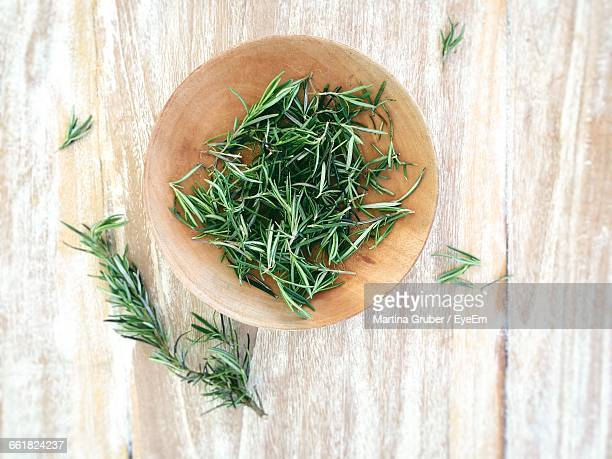 top view of fresh rosemary in bowl on wooden table - ローズマリー ストックフォトと画像