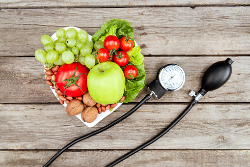 top view of fresh various vegetables, fruits and blood pressure gauge on wooden surface, healthy eating concept 819720684