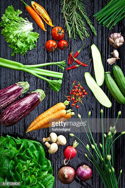 Top view of fresh vegetables and spices on dark background