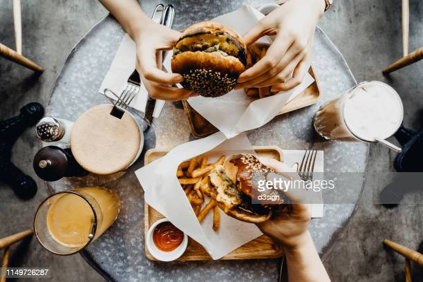top view of friends having a good time eating burgers with french fries and drinks in a cafe - restaurant stock pictures, royalty-free photos & images