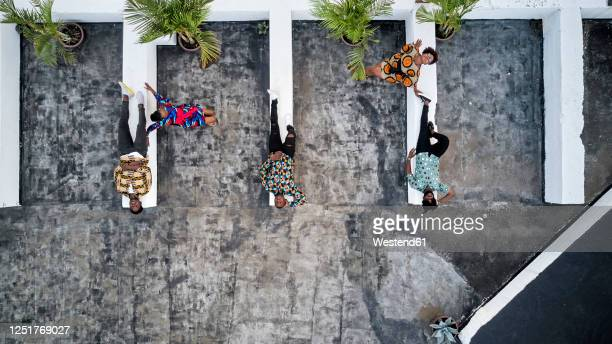 top view of friends in colorful clothes lying on roof terrace - mozambique stock pictures, royalty-free photos & images