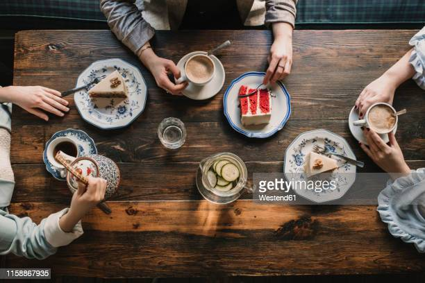 top view of friends sitting at wooden table in a cafe - nagerecht stockfoto's en -beelden