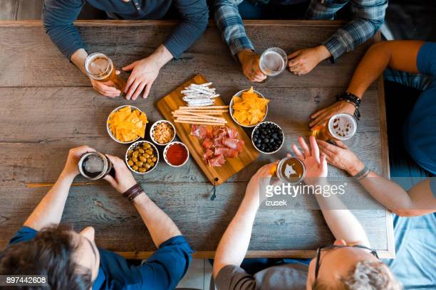 Top view of friends sitting over beer at the table in pub