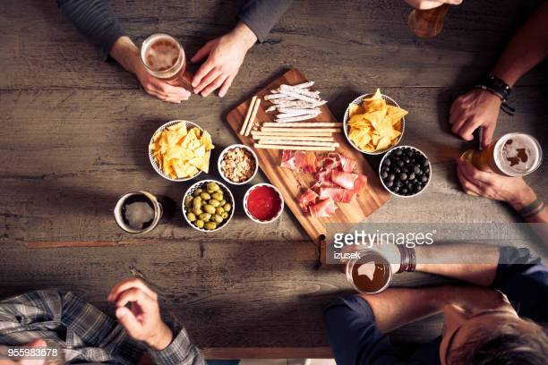 top view of friends sitting over beer at the table in pub - wood table top stock photos and pictures