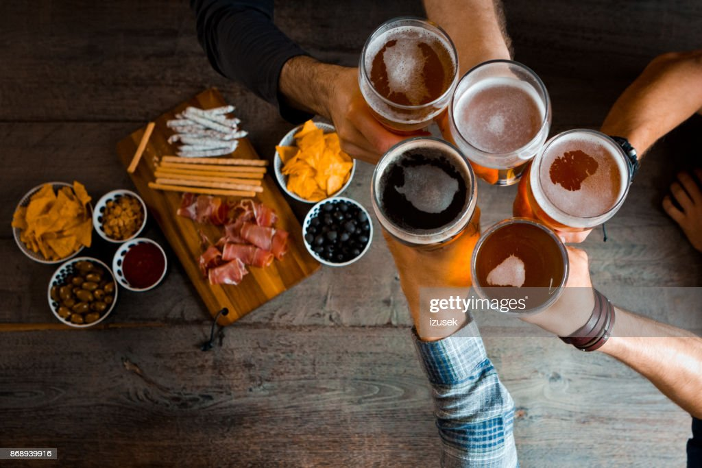 Top view of friends toasting with beer glasses in the pub : Stock Photo