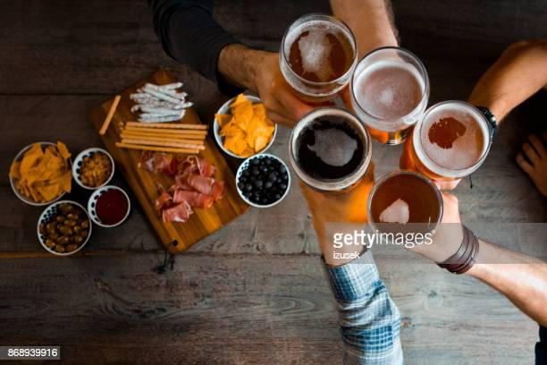 top view of friends toasting with beer glasses in the pub - refreshment stock pictures, royalty-free photos & images