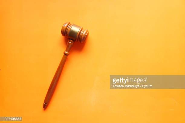 top view of gavel on orange background . - gavel stock pictures, royalty-free photos & images