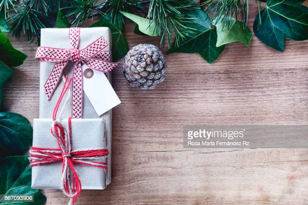 Top view of gift boxes wrapped in brown paper with rustic bow tie on wooden background. Top View and copy space.