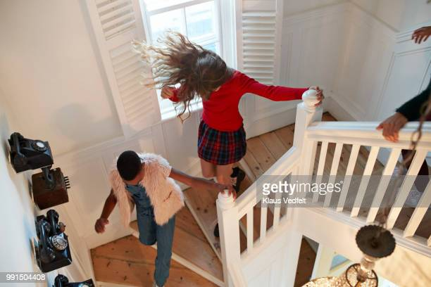 Top view of girls running down staircase, at home