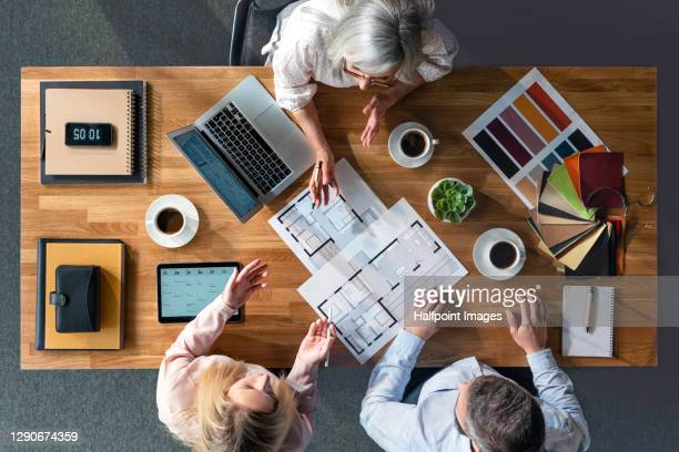top view of group of architects working at desk, discussing issues. - coworking stock pictures, royalty-free photos & images