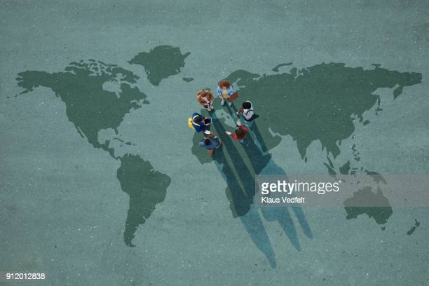 Top view of group of people, standing on worldmap, painted on asphalt