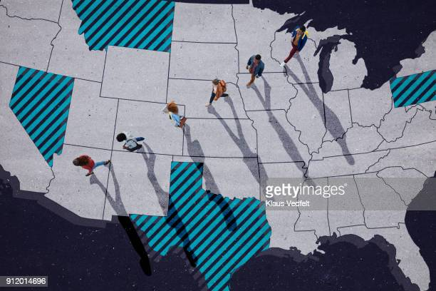 Top view of group of people, walking across United States map, painted on asphalt