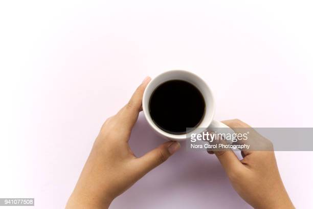 top view of hand holding black coffee in cup over white background - caffeine stock pictures, royalty-free photos & images
