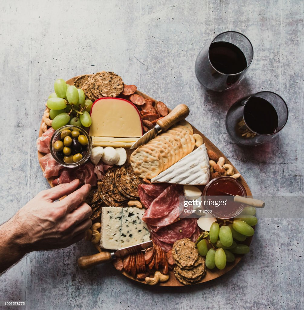 Top view of hand taking food off charcuterie board on stone counter. : Stock Photo