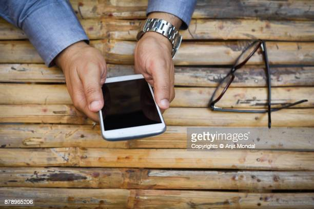 Top View of Hands Holding White Mobile Phone Wooden Background Blank Mobile Screen