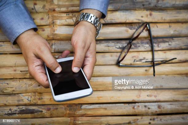 top view of hands using white mobile phone wooden background blank mobile screen - mobile stockfoto's en -beelden