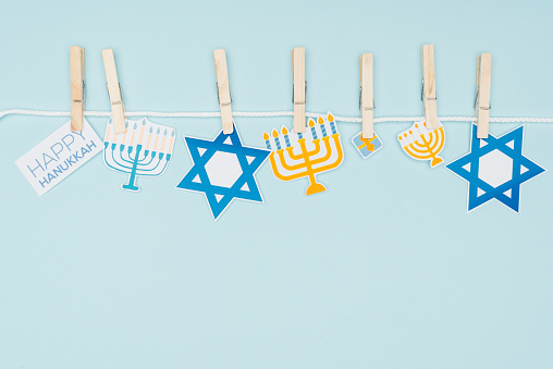 top view of hannukah holiday paper signs pegged on rope isolated on blue, hannukah concept 1061622916