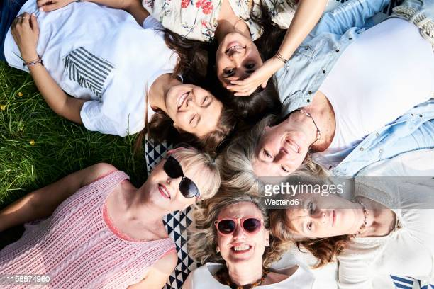 top view of happy group of women lying in a meadow - mature adult stock pictures, royalty-free photos & images