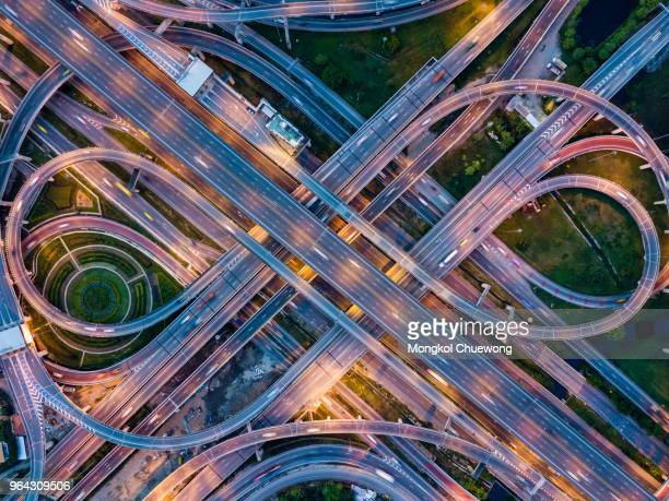 top view of highway road junctions at night. the intersecting freeway road overpass the eastern outer ring road of bangkok, thailand. - complicated stock photos and pictures