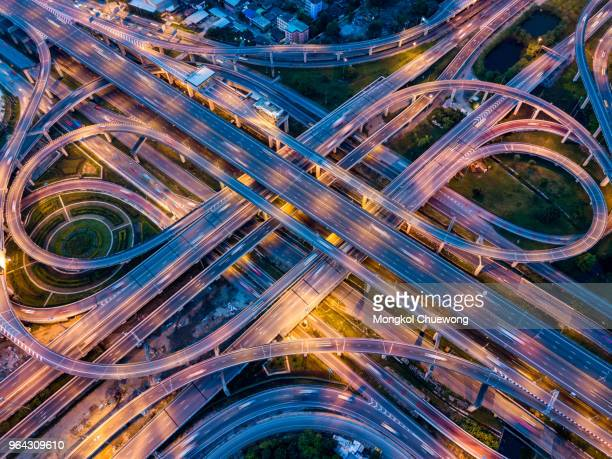 top view of highway road junctions at night. the intersecting freeway road overpass the eastern outer ring road of bangkok, thailand. - flyover stock pictures, royalty-free photos & images