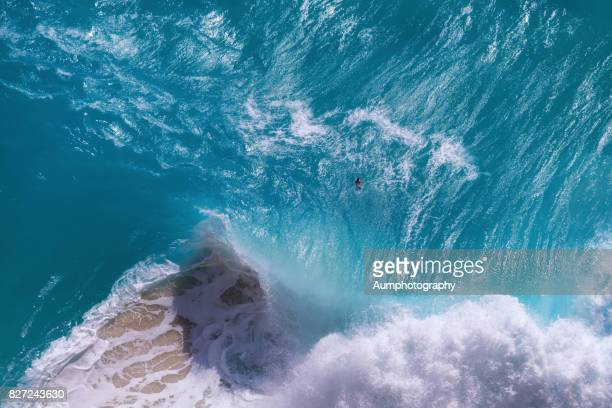 Top view of huge ocean waves at Kelingking Beach, Nusa Penida Island, Indonesia.