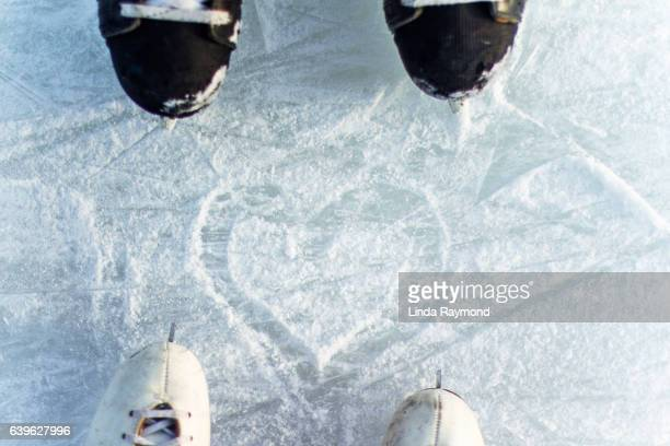 Top view of ice skating of a boy and a girl with a heat shape traced on the ice