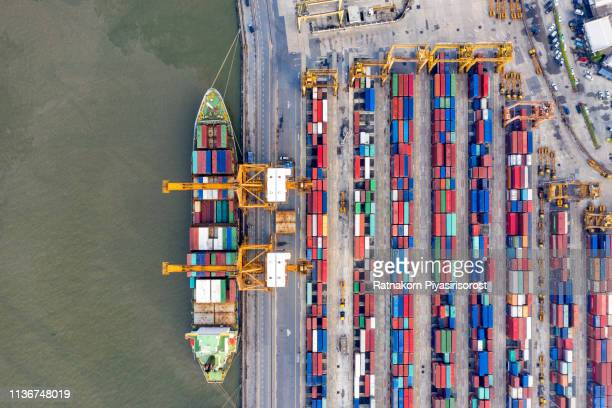 top view of international port with crane loading containers in import export business logistics - hafen stock-fotos und bilder